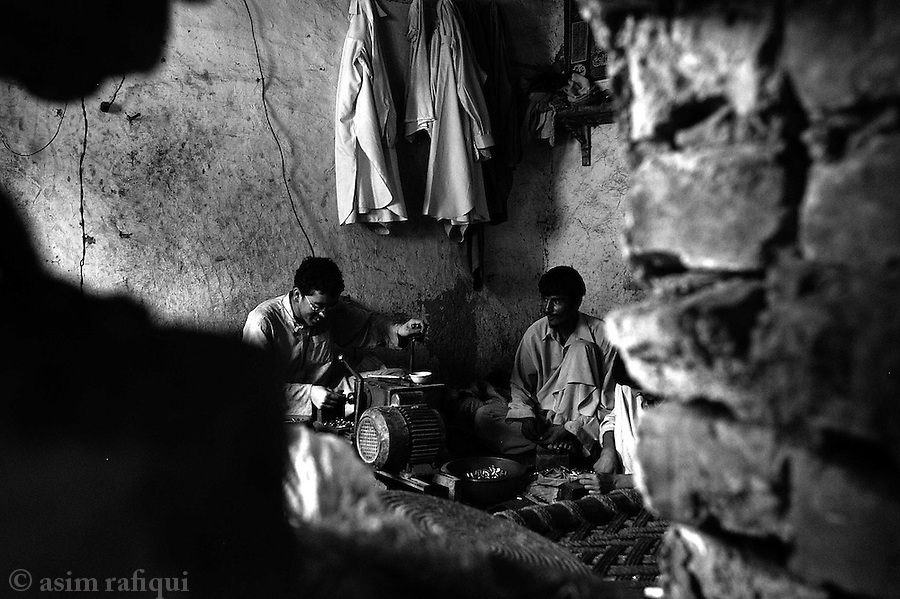 workers cut bullets for kalashnikovs and hand held pistols at a factory.  darra adam khel, tribal areas, pakistan.  september 2003&amp;#xA;&amp;#xA;copyright asim rafiqui 2003<br />