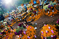 Mexican families gather at the cemetery, bringing flowers and food offerings, to honor their deceased relatives during the Day of the Dead festivities in Tzurumútaro, Michoacán, Mexico, 3 November 2014. Day of the Dead ('Día de Muertos') is a syncretic religious holiday, celebrated throughout Mexico, combining the death veneration rituals of the ancient Aztec culture with the Catholic practice. Based on the belief that the souls of the departed may come back to this world on that day, people gather on the gravesites praying, drinking and playing music, to joyfully remember friends or family members who have died and to support their souls on the spiritual journey.