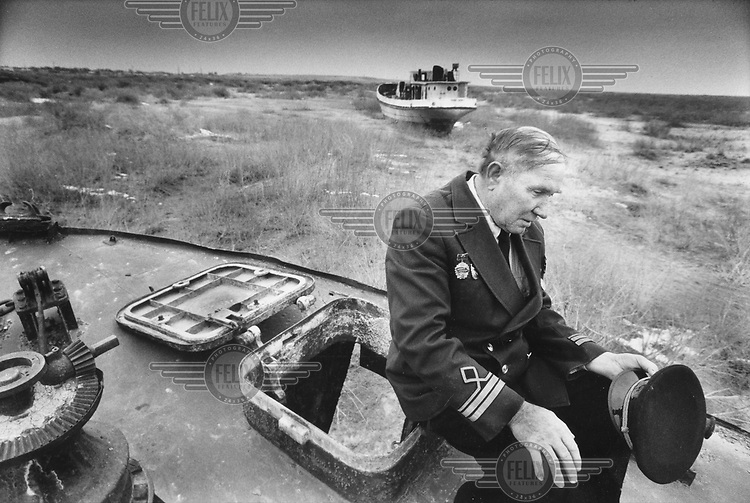 © Dieter Telemans / Panos Pictures..Muynak, on the shores of the Aral Sea, UZBEKISTAN..Sergei Bakajoesjin Lipatovitsj (66), harbour master without a harbour. Sergei remembers his training as a captain with in the Soviet Union?s Black Sea fleet. ?I was the only crew member from Karakalpak?, he said,.proudly referring to his Uzbek republic. When he left the service he brought the stripes he had earned to the Aral Sea where he lent the young fishermen the benefits of his shipping experience. Nowadays both he and his trainees are unemployed. The sea has receded over 100 kilometres from the harbour village of Muynak. Photo:  Dieter Telemans / Panos Pictures/Felix Features