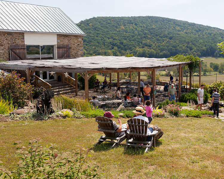 Adirondack chairs are positioned in the lawn above the patio at Hillsborough Vineyards -- offering fabulous views of the surrounding valley countryside within easy listening distance to year live music on the covered patio below.