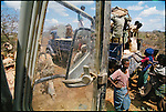 U.S. Marines of the U.N.'s Operation Restore Hope escort the delivery of food aid from CARE to far-flung villages the agency hadn't been able to reach safely for months. Outside Baidoa, Somalia. January 1993