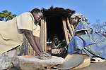 Sezerina Tiyu (left) grinds sorghum with the help of Joice Kiden (right) in the Southern Sudan village of Yondoru. Families here are rebuilding their lives after returning from refuge in Uganda in 2006 following the 2005 Comprehensive Peace Agreement between the north and south. Both women are United Methodist. NOTE: In July 2011, Southern Sudan became the independent country of South Sudan