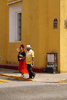Colorfully dressed couple crossing a street in the city of Veracruz, Mexico