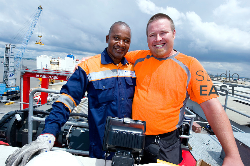 KoneCranes Site Manager Jani RIIKONEN (right) and worker Julien N'DAH (left) poses for a photograph on top of a new KoneCranes RTG crane being assembled in Abidjan Container Terminal, in Abidjan, Ivory Coast, on November 3, 2010. Photo by Lucas Schifres/Pictobank