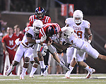 Mississippi quarterback Bo Wallace (14) is tackled by Texas' Adrian Phillips (17) and Texas' Kenny Vaccaro (4) at Vaught-Hemingway Stadium in Oxford, Miss. on Saturday, September 15, 2012. (AP Photo/Oxford Eagle, Bruce Newman)