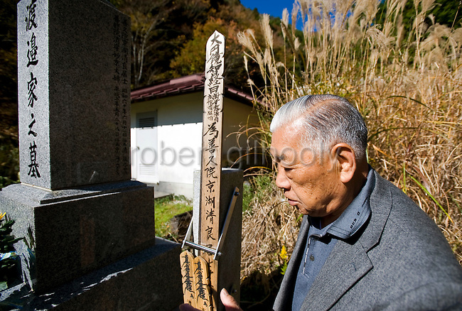 Yoshifumi Yamada, 84, chairman of Lake Shouji Touism Association, walks through a cemetery in which the remains of unidentifiable suicide victims are interred   near Aokigahara Jukai, better known as the Mt. Fuji suicide forest, which is located at the base of Japan's famed mountain west of Tokyo, Japan on 03 Nov. 2009.
