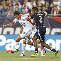 D.C. United midfielder Chris Pontius (13) on the attack as New England Revolution defender Andrew Farrell (2) defends. In a Major League Soccer (MLS) match, the New England Revolution (blue) tied D.C. United (white), 0-0, at Gillette Stadium on June 8, 2013.