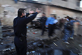 KIRKUK, IRAQ: A policeman shouts at people in the street at the scene of a triple car bomb...At 6 am, three car bombs detonated in the peaceful Kurdish neighborhood of Imam Kasimin Kirkuk.  There were 17 casualties.  Kirkuk is Iraq's most ethnically mixed city and is one month away from a volatile census that will determine the future of the city...Photo by Ari Mohammad/Metrography.