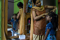 Sharda ties her younger sister's hair in the brothel where they live with their mother, a commercial sex worker, in the Mau Red Light area in Mau, Uttar Pradesh, India on 17 November 2013. Commercial Sex Worker's children growing up in the brothels are pampered and groomed to be the next generation of prostitutes, traffickers or pimps, however, Sharda is being married off into a community outside, sealing her future away from this vicious cycle, and her mother is keen to get all her 5 children out of the prostitution community.