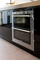 In the kitchen a stainless steel oven is set in cupboards faced with black high-gloss parapan