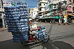 A man hauls a large bundle of sandals on his motorbike in District 11 in Ho Chi Minh City, Vietnam. Aug. 16, 2011.