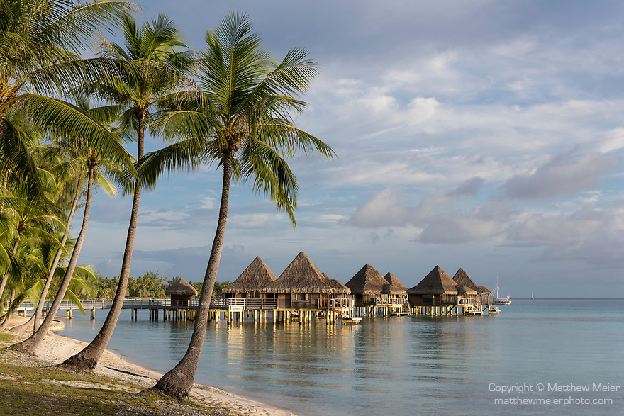 Rangiroa Atoll, Tuamotu Archipelago, French Polynesia; view of the overwater bungalows at the Hotel Kia Ora Resort and Spa in late afternoon sunlight