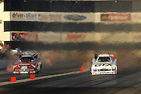 Nov 3, 2007; Pomona, CA, USA; NHRA funny car driver Mike Ashley (left) races alongside Ashley Force during qualifying for the Auto Club Finals at Auto Club Raceway at Pomona. Mandatory Credit: Mark J. Rebilas-US PRESSWIRE