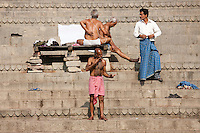 Men bathing at Dharbanga Ghat by the Ganges River in City of Varanasi, Benares, Northern India