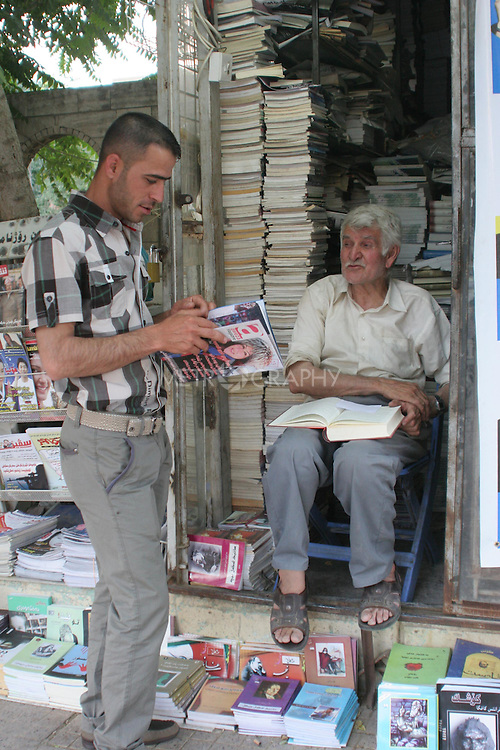 Anwar Brzo, 71, is a retired primary school teacher who sells books and magazines out of a shack where he lives alone with his cat. Anwar works from 7-9:30 every day - with only two days off per year. Salm Street in Sulaymaniyah, next to the public garden.<br />