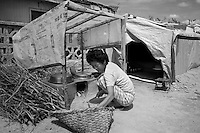 A woman prepares a meal in a temporary tarpaulin shelter in Pongchon county, DPRK during a field visit by national and international Red Cross officials on Saturday August 27 2011. Consecutive floods caused by heavy rainfall and strong winds, together with the impact of typhoon Muifa which struck in early August, resulted in the destruction or severe damage of over 9,500 houses, rendering more than 25,000 people homeless between June 23 and August 9, according to data provided by the DPRK government. While flood damage was reported throughout the country, south and north Hwanghae provinces have been worst hit by the repeated flooding, leaving an already vulnerable population in a critical condition.  Photo by Morten Hvaal/Felix Features for IFRC.