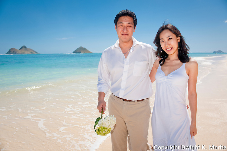 Asian bride and groom pose arm in arm on Lanikai beach as they look forward to their life as a married couple following their wedding.