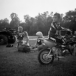 A young boys sits on his dirt bike with his family in the background in rural Sussex County Delaware.