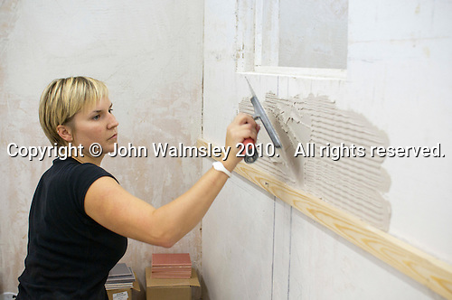 Student doing a course in tiling applying the adhesive.  Able Skills in Dartford, Kent, runs courses in construction industry skills like, bricklaying, carpentry and tiling.