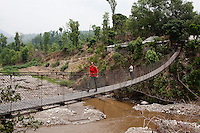 The Guardian reporter Zoe Williams crosses the river at Gangate Village, Sathakhani Bidishi, Surkhet district, Western Nepal, on 30th June 2012. In Surkhet, StC partners with Safer Society, a local NGO which advocates for child rights and against child marriage.  Photo by Suzanne Lee for Save The Children UK