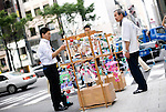 A young businessman looks at the several dozen Edo furin, or glass wind chimes, which are being sold by Yoshitomo Sasaki on  streets of chic Ginza district in Tokyo, Japan. The chimes, which date back more than 200 years in Japan, were traditionally carried around town dangling from  bamboo poles by sellers. Sasaki is one of a few people who continue this trend.A admires Edo furin, or glass wind chimes, displayed on a wooden frame by seller Yoshitomo Sasaki in the chic Ginza district in Tokyo, Japan. The chimes, which date back more than 300 years in Japan, were traditionally carried around town dangling from  bamboo poles by sellers. Sasaki is one of a few people who continue this trend.