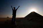 A male tourist raises his arms in praise toward the ancient site of the Red Pyramid, the world's oldest true pyramid, also known as the North Pyramid, located 10km south of Saqqara in Dahshur, Egypt.