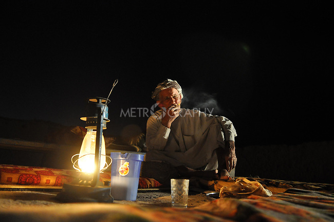 DOWDA, IRAQ:  Mam Ibrahim smokes a cigarette by lamplight...Iraqi forces decimated the Dowda area in Germian during the 1988 Anfal genocidal campaign against the Kurds.  Daily life continues is this extremely harsh part of Iraq...Photo by Aram Karim/Metrography