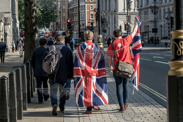 'Leave' (the EU) supporters, draped in Union Jack flags, walk along Whitehall after the EU referendum results show a victory for the Brexit side.