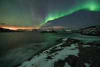 Northern Lights shine in sky above Gimsøystraumen, near Henningsvaer, Austvågøy, Lofoten Islands, Norway