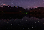 Night brings forth stars above the Mission mountain range in Western Montana seen from the Kicking Horse Reservoir.