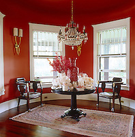 The living room is painted a lush red which creates a perfect backdrop for a collection of objects displayed on a pedestal table