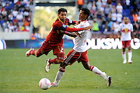 Paulo Araujo Jr. (23) of Real Salt Lake jumps over a tackle by Roy Miller (7) of the New York Red Bulls. The New York Red Bulls and Real Salt Lake played to a 0-0 tie during a Major League Soccer (MLS) match at Red Bull Arena in Harrison, NJ, on October 09, 2010.