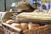 Loaves of artisanal bread for sale at a bakery.
