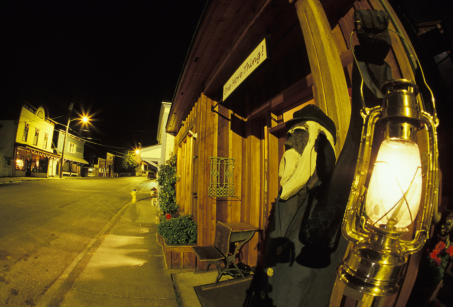 Wood captain statue holding lit lantern and Western-style store fronts at night, Coupeville, Washington