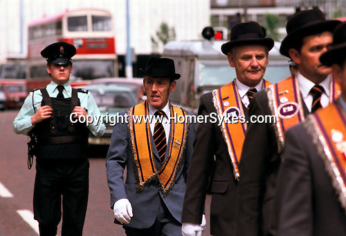 Armed policeman walks behind an Orange Day Parade, Belfast Northern Ireland 1980s. UK