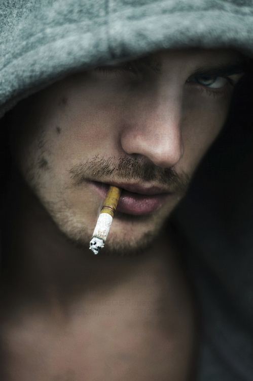 A young man wearing a hoody smoking a cigarette