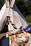 Close up of  Native American Pow Wow Regalia on car and tepee in background.  Examples of ethnic pride, heritage, celebration, and traditional folk art crafts. ..
