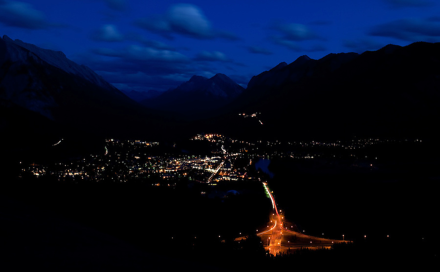 An aerial view of the city of Banff is seen from the Mt. Norquay road with a dark blue sky and clouds in motion in the evening.