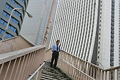 "An office worker, known as a ""salaryman"", pauses to work his mobile teklephone in Nishi-Shinjuku skyscraper district of Tokyo, Japan"