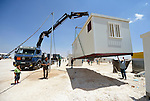 A modular house is lowered into place in the Zaatari refugee camp near Mafraq, Jordan. Established in 2012 as Syrian refugees poured across the border, the camp held more than 80,000 refugees by early 2015, and was rapidly evolving into a permanent settlement. Tents were steadily being replaced by modular living units, or caravans. The ACT Alliance provides a variety of services to refugees living in the camp.