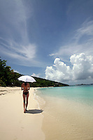 September 2008: Woman holding a white umbrella in clear ocean water on St. John US Virgin Islands beach scenes.  Stock photos available.