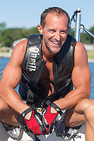 handsome athletic man smiling while sitting on a waterski boat in The Hamptons