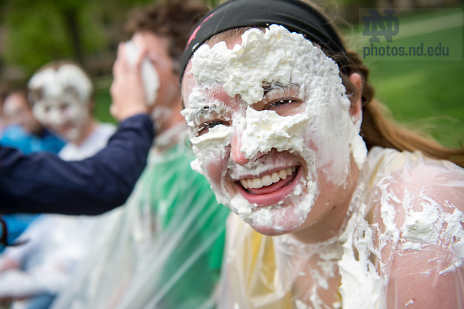 """April 28, 2017; Lydia Costello, outgoing president of Lyons Hall, smiles after being 'pied' with a whipped cream pie for the """"Pie Your President"""" fundraiser, an annual event organized by Walsh Hall to raise money for the Ronald McDonald House of South Bend. (Photo by Matt Cashore/University of Notre Dame)"""