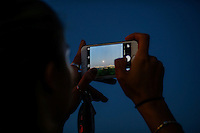 A woman takes a picture of Blue moon with her cellphone as the moon rises next to the Empire State Building and middle Manhattan while it is seen from New Jersey.  07/31/2015. Eduardo MunozAlvarez/VIEWpress