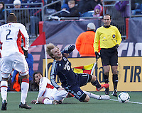 New England Revolution forward Juan Toja (7) tackles Sporting Kansas City defender Seth Sinovic (15).  In a Major League Soccer (MLS) match, Sporting Kansas City (blue) tied the New England Revolution (white), 0-0, at Gillette Stadium on March 23, 2013.