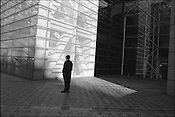 A worker stands in ther shade outside a modern office building near the American Embassy, Tokyo, japan.