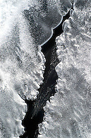 A frigid creek runs swiftly below the cracks in the ice in this abstract..
