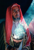 A Bedouin man in his tent holding an incense burner in Riyadh, Saudi Arabia