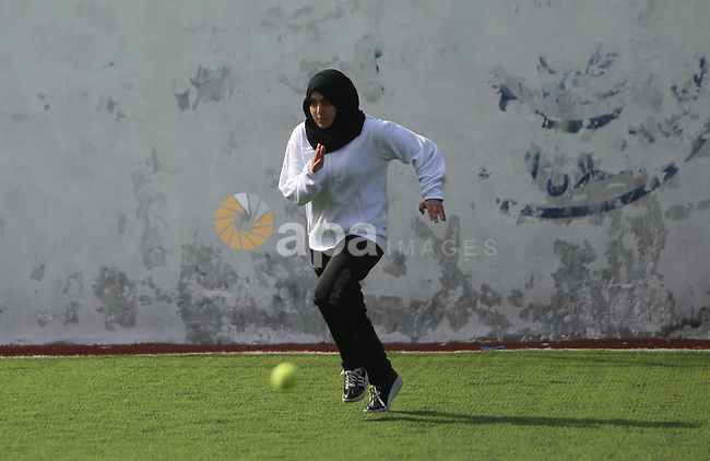 """A Palestinian girl takes part in Baseball training, in Gaza city, on February 20, 2017. Baseball is a bat-and-ball game played between two teams of nine players each, who take turns batting and fielding. Baseball is thought to have originated as a game called """"rounders"""" in England and gained popularity in the United States in the early 1900s. It has gone by many names in the past, including """"town ball,"""" """"goal ball,"""" round ball,"""" and simply """"base,"""" just to name a few. Photo by Ashraf Amra"""