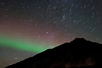 Aurora borealis, (northern lights) and starry sky over the Brooks mountain range, Arctic, Alaska.